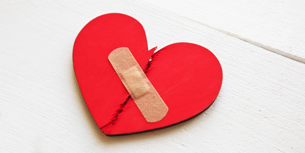 Two parts of red broken wooden heart taped by a patch. Concept o